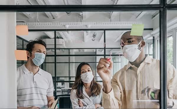 team wearing masks around a whiteboard